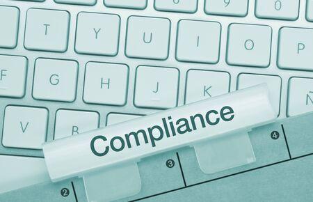 Compliance Written on Green Key of Metallic Keyboard. Finger pressing key.