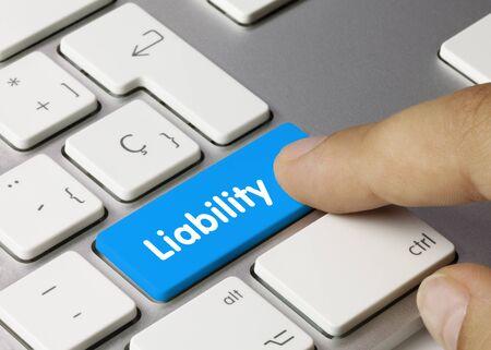 Liability Written on Blue Key of Metallic Keyboard. Finger pressing key.