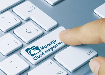 Manage Cloud migration Written on Blue Key of Metallic Keyboard. Finger pressing key.