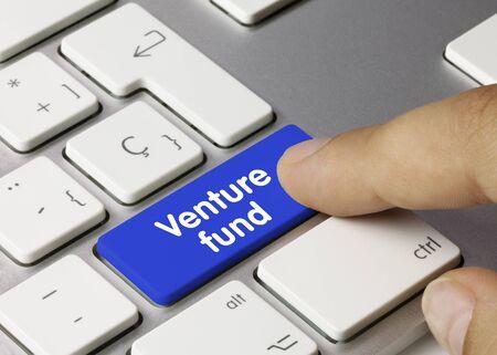 Venture fund Written on Blue Key of Metallic Keyboard. Finger pressing key.