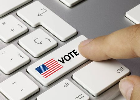 VOTE Written on White Key of Metallic Keyboard. Finger pressing key.