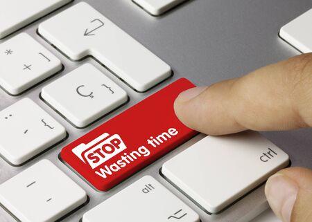 Stop Wasting time Written on Red Key of Metallic Keyboard. Finger pressing key.