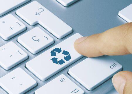 Recycle  Written on Blue Key of Metallic Keyboard. Finger pressing key.