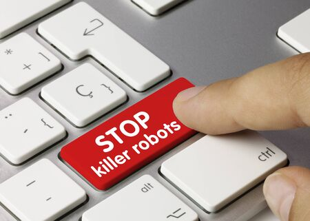 Stop killer robots Written on Red Key of Metallic Keyboard. Finger pressing key.