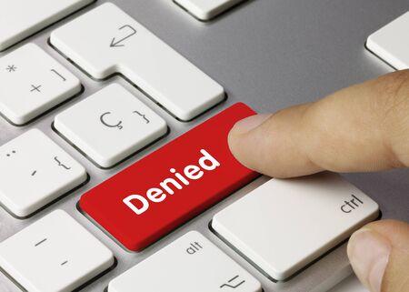 Denied Written on Red Key of Metallic Keyboard. Finger pressing key. Foto de archivo