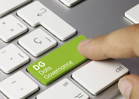 DG data governance Written on Green Key of Metallic Keyboard. Finger pressing key.