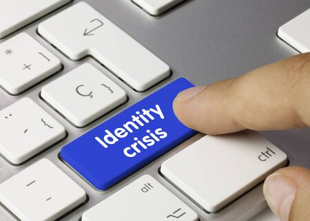 Identity crisis  Written on Blue Key of Metallic Keyboard. Finger pressing key. Foto de archivo