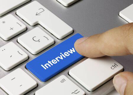 Interview Written on Blue Key of Metallic Keyboard. Finger pressing key.