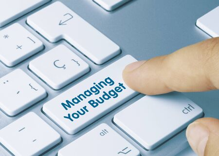 Managing Your Budget  Written on Blue Key of Metallic Keyboard. Finger pressing key. Banco de Imagens