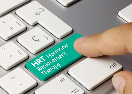 HRT Hormone Replacement Therapy Written on Green Key of Metallic Keyboard. Finger pressing key.
