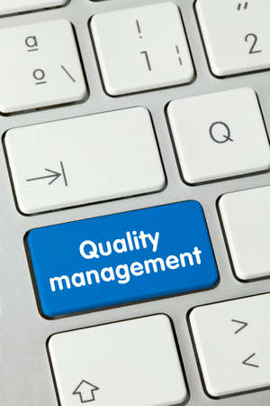 Quality management Written on Blue Key of Metallic Keyboard. Finger pressing key.