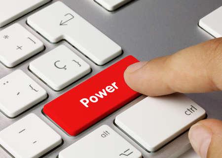 Power Written on Red Key of Metallic Keyboard. Finger pressing key. Banco de Imagens