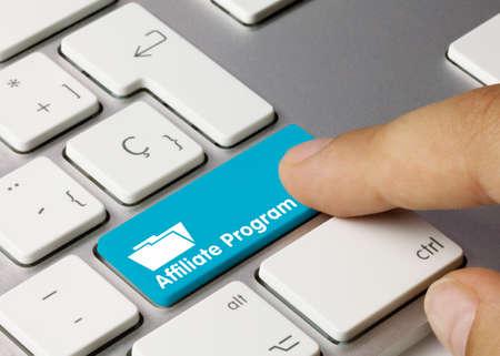 Affiliate program Written on Blue Key of Metallic Keyboard. Finger pressing key.