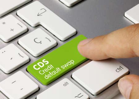 Credit default swap Written on Green Key of Metallic Keyboard. Finger pressing key. Imagens