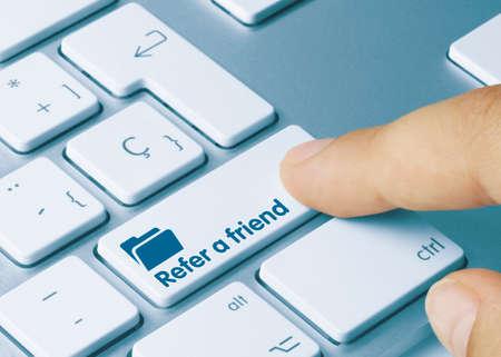 Refer a friend Written on Blue Key of Metallic Keyboard. Finger pressing key. Imagens