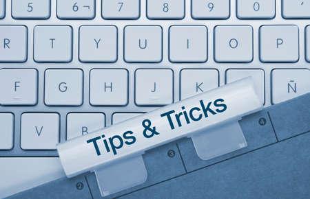 Tips & tricks Written on Blue Key of Metallic Keyboard. Finger pressing key.