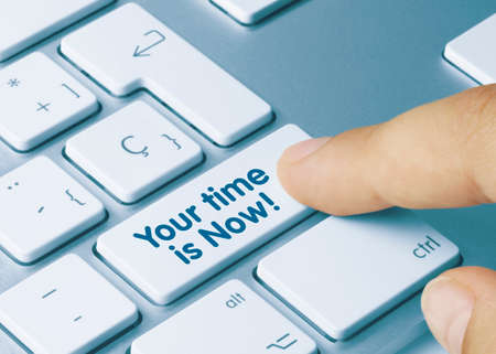Your time is now! Written on Blue Key of Metallic Keyboard. Finger pressing key. Banque d'images