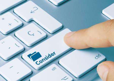 Consider Written on Blue Key of Metallic Keyboard. Finger pressing key.