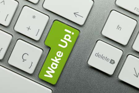 Wake up! Written on Green Key of Metallic Keyboard. Finger pressing key.