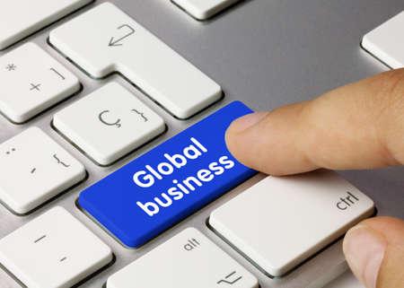 Global business Written on Blue Key of Metallic Keyboard. Finger pressing key.
