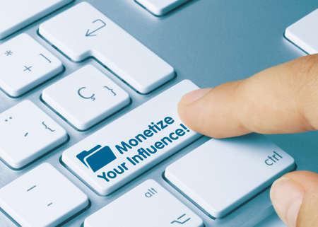 Monetize Your Influence! Written on Blue Key of Metallic Keyboard. Finger pressing key.