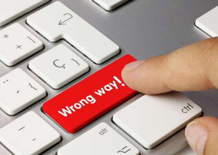 Wrong way Written on Red Key of Metallic Keyboard. Finger pressing key.