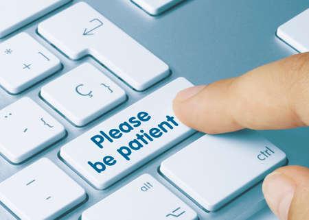 Please be patient Written on Blue Key of Metallic Keyboard. Finger pressing key.