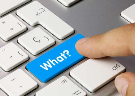 Que? Written on Blue Key of Metallic Keyboard. Finger pressing key. Reklamní fotografie