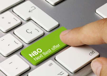 NBO Next Best offer Written on Green Key of Metallic Keyboard. Finger pressing key. 免版税图像