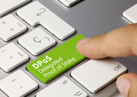 DPoS Delegated proof of stake Written on Green Key of Metallic Keyboard. Finger pressing key. 免版税图像