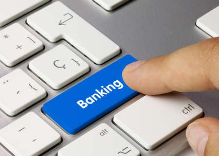Banking Written on Blue Key of Metallic Keyboard. Finger pressing key.