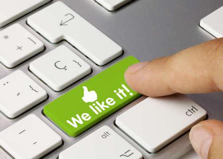 We like it! Written on Green Key of Metallic Keyboard. Finger pressing key. Stock Photo