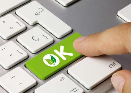 OK green Written on Green Key of Metallic Keyboard. Finger pressing key.