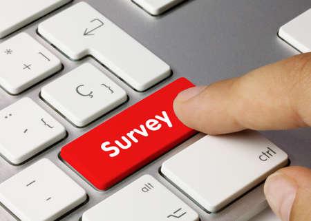 Survey Written on Red Key of Metallic Keyboard. Finger pressing key.