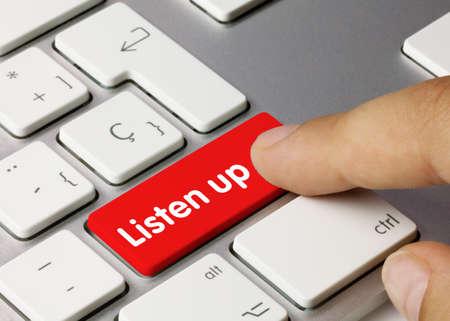 Listen up Written on Red Key of Metallic Keyboard. Finger pressing key. 免版税图像