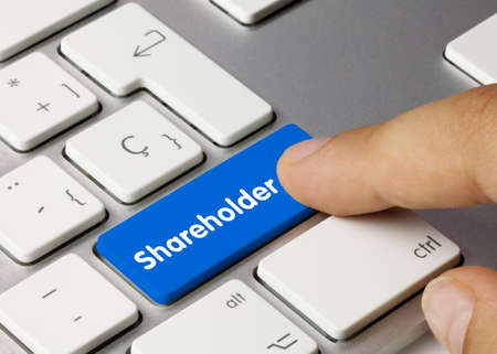 Shareholder Written on Blue Key of Metallic Keyboard. Finger pressing key.