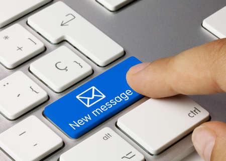 New message Written on Blue Key of Metallic Keyboard. Finger pressing key.