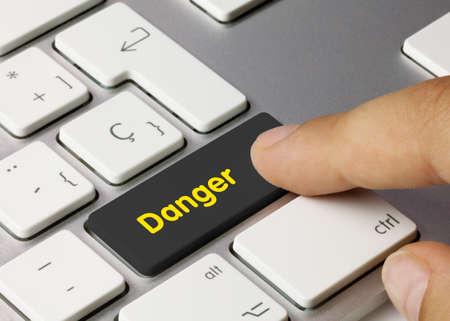 Danger Written on Black Key of Metallic Keyboard. Finger pressing key. 免版税图像