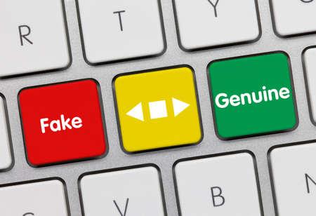 Fake or Genuine Written on Red-Yellow-Green Key of Metallic Keyboard. Finger pressing key.
