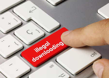 illegal downloading Written on Red Key of Metallic Keyboard. Finger pressing key.