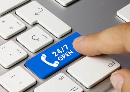 24 hours open Written on Blue Key of Metallic Keyboard. Finger pressing key. 免版税图像