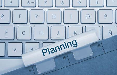 Planning Written on Blue Key of Metallic Keyboard. Finger pressing key.