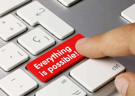 Everything is possible! Written on Red Key of Metallic Keyboard. Finger pressing key. Archivio Fotografico