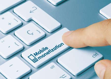 Mobile Monetization Written on Blue Key of Metallic Keyboard. Finger pressing key.