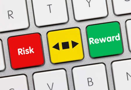 Risk and reward Written on Red-Yellow-Green Key of Metallic Keyboard. Finger pressing key. Archivio Fotografico
