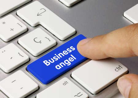 Business angel Written on Blue Key of Metallic Keyboard. Finger pressing key. Archivio Fotografico