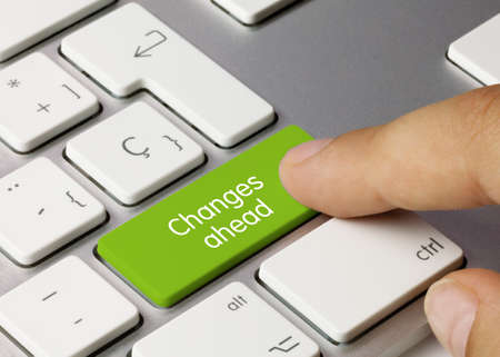 Changes ahead Written on Green Key of Metallic Keyboard. Finger pressing key. Stock Photo