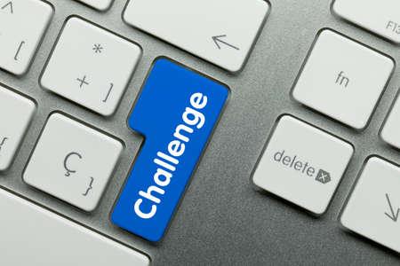 Challenge Written on Blue Key of Metallic Keyboard. Finger pressing key.