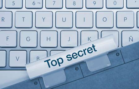 Top secret Written on Blue Key of Metallic Keyboard. Finger pressing key. Banco de Imagens