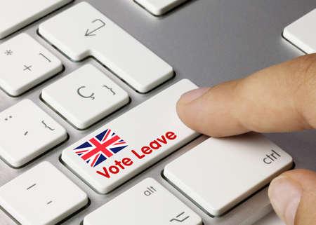 Vote leave Written on White Key of Metallic Keyboard. Finger pressing key.